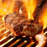 Nötköttsteak på gallret med flammor. Arkivbild
