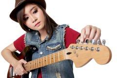 Nätt asiatisk flicka som trimmar hennes gitarr, på vit bakgrund Royaltyfri Fotografi