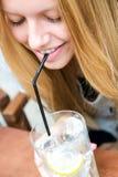 Nätt blond flicka som tar en drink på en terrass Royaltyfri Foto