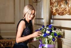 Nätt blond kvinna med blommorna, inomhus Royaltyfria Bilder