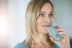 Nätt blond kvinna som dricker ett exponeringsglas av vatten Arkivbild