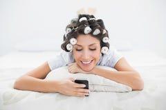 Nätt brunett i hårrullar som ligger på hennes säng som överför en text Fotografering för Bildbyråer