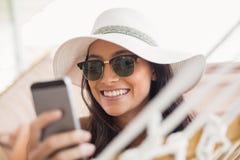 Nätt brunett som kopplar av på en hängmatta och smsar med hennes mobiltelefon Royaltyfri Bild