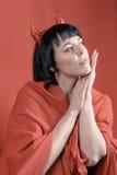 Nätt brunettkvinna med hornen för röd jäkel Royaltyfria Bilder