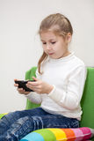 Nätt Caucasian flicka som spelar leken på mobiltelefonen som inomhus sitter Arkivbild