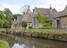 Nätt engelsk by med stenhus, flod, lösa blommor Royaltyfria Foton