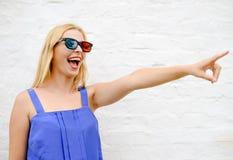 Nätt flicka i exponeringsglas som 3d är upphetsade och pekar på Arkivfoton