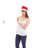Nätt flicka i hållande affisch för santa hatt Arkivbild