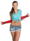 Nätt flicka i kortslutningar och röd skjorta som rymmer Arkivbilder