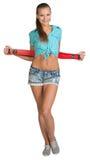 Nätt flicka i kortslutningar och röd skjorta som rymmer Royaltyfri Fotografi