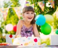 Nätt flicka med kakan på födelsedagpartiet Arkivbilder