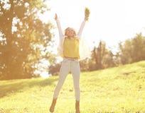 Nätt gladlynt kvinna som har gyckel i solig höstdag Fotografering för Bildbyråer