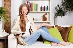 Nätt kvinna som förargas om hållande ögonen på TV Arkivfoto