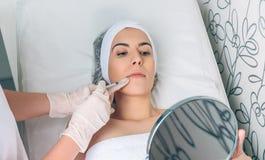 Nätt kvinna som ser kantbehandling i en spegel Arkivbild