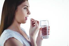Nätt kvinna som tar den vita preventivpilleren Arkivfoto