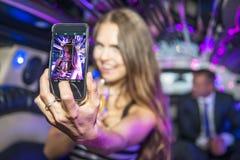 Nätt kvinna som tar en selfie i en limousine Royaltyfri Bild