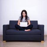Nätt kvinnasammanträde på soffan och användabärbara datorn hemma Arkivfoto