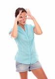 Nätt kvinnlig i kort jeans som gör en gest exponeringsglas Royaltyfri Fotografi