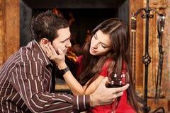 Kvinnan smeker henne manen nära spis Royaltyfri Bild