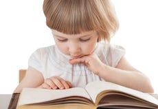 Nätt liten flicka som läser en bok Arkivfoto