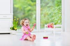 Nätt litet barnflicka som spelar maracas i vitt rum Royaltyfria Bilder