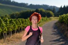 Nätt livlig rödhårig mankvinna som joggar ut Royaltyfri Foto