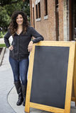 Nätt lockig Haired kvinna med svart tavla Arkivfoton