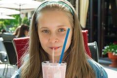 Nätt lycklig flicka som dricker jordgubbesmoothien Fotografering för Bildbyråer