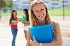 Nätt studentflicka med några vänner på universitetsområdet Arkivfoton