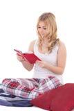 Nätt tonårs- flicka, i att sitta för pyjamas och isolerad läsebok Arkivfoto