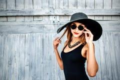 Nätt ung flicka som står nära träväggen i svart swimwear Fotografering för Bildbyråer