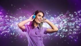Nätt ung kvinna med hörlurar som lyssnar till musik Arkivbild