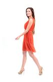Nätt ungt kvinnligt modellerar i klänningen som går på bakgrund och att le för vit Arkivbild