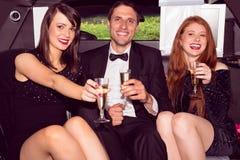 Nätta flickor med dammannen i limousineet Royaltyfri Foto