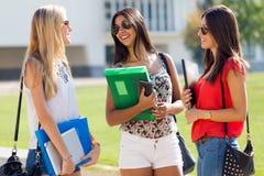 Nätta studentflickor som har gyckel på universitetsområdet Royaltyfri Fotografi