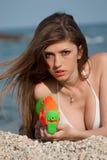 Nätta unga kvinnor som spelar med vattenvapnet på stranden Arkivfoto
