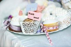 Nätta vita muffin snör åt in lögn på en platta Arkivfoto
