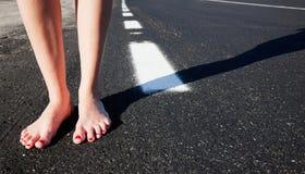 Nu-pieds et route images libres de droits