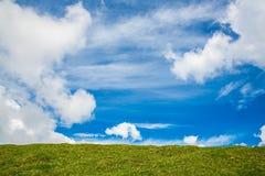 Nuage blanc en ciel bleu avec l'herbe verte Image libre de droits