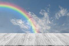 Nuage de ciel bleu avec la terrasse et l'arc-en-ciel en bois Photo libre de droits