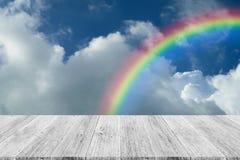 Nuage de ciel bleu avec la terrasse et l'arc-en-ciel en bois Image stock