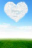 Nuage de coeur sur le ciel bleu et le champ vert Image libre de droits
