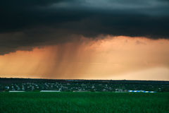 Nuage de tempête avec la pluie au coucher du soleil, au-dessus du village Images stock