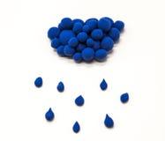 Nuage en gros plan de pâte à modeler bleue avec des gouttes de pluie sur un fond blanc Photo libre de droits