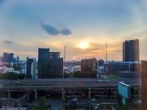 Nuage et ciel de soirée au-dessus d'autoroute urbaine et d'édifice haut moderne Image stock