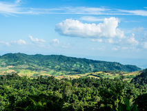 Nuage formé par avion au-dessus de montagne verte Image libre de droits