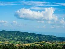 Nuage formé par avion au-dessus de montagne verte Photographie stock libre de droits