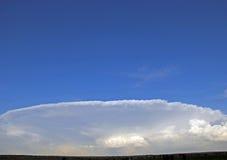 Nuage lenticulaire formé comme plat blanc contre le ciel bleu Photographie stock libre de droits