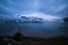 Nuages à l'heure bleue de crépuscule, au lac et à la montagne couronnée de neige, hiver froid, paysage de nord de fjord Image stock