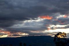 Nuages éclairés par les rayons de soleil rouges du coucher du soleil images libres de droits